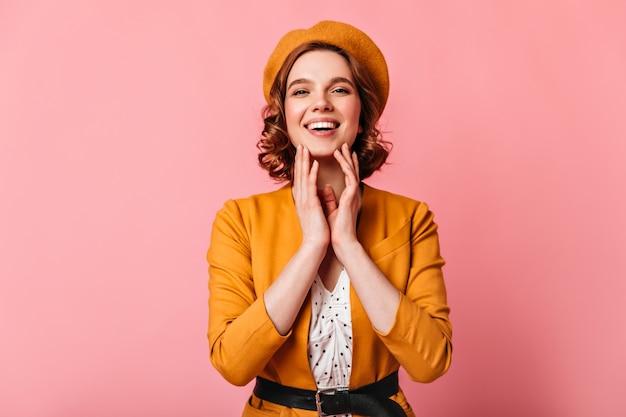 Vorderansicht der lachenden entzückenden frau in der gelben baskenmütze. studioaufnahme des lächelnden mädchens mit dem welligen haar, das auf rosa hintergrund aufwirft.