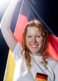 Vorderansicht der lächelnden frau, die deutsche flagge hält