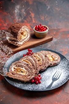Vorderansicht der leckeren keksrollen mit früchten auf dunkler oberfläche