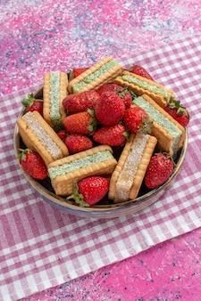 Vorderansicht der leckeren waffelkekse mit frischen roten erdbeeren an der rosa wand