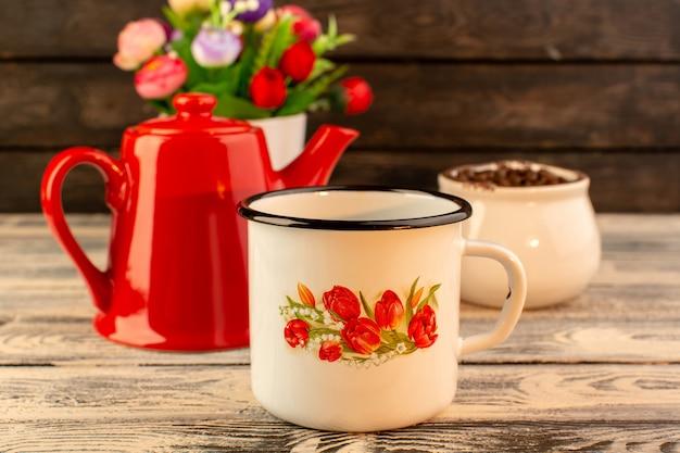 Vorderansicht der leeren tasse mit den braunen kaffeesamen und blumen des roten kessels auf dem hölzernen schreibtisch
