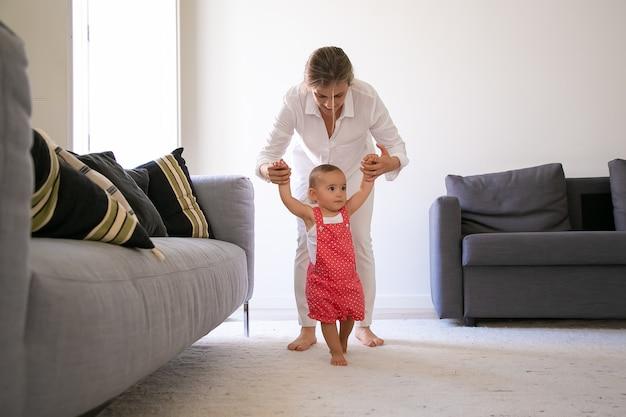 Vorderansicht der mutter, die kleine mädchenhände hält und hilft, zu gehen. nettes barfußes baby in roten latzhose-shorts, die lernen, im wohnzimmer mit hilfe der mutter zu gehen. familienzeit und erster schritt konzept