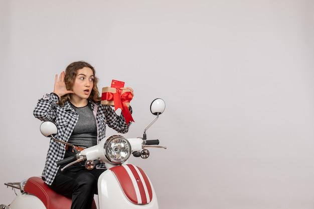 Vorderansicht der neugierigen jungen frau auf moped, das geschenk hält, das etwas auf grauer wand hört