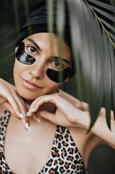 Vorderansicht der niedlichen frau mit augenklappen unter palme. schönes weibliches modell, das auf tropischem hintergrund aufwirft.
