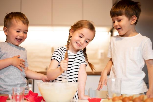 Vorderansicht der niedlichen geschwister, die zu hause kochen