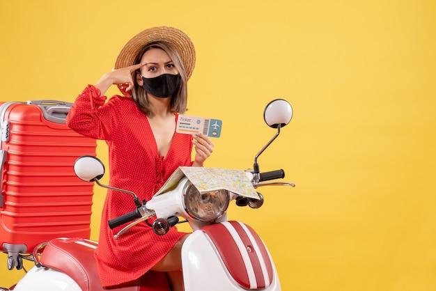 Vorderansicht der niedlichen jungen dame mit schwarzer maske auf moped-haltekarte