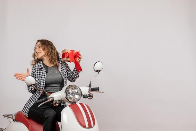 Vorderansicht der niedlichen jungen frau auf moped, das geschenk auf grauer wand hält