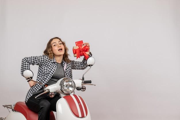 Vorderansicht der niedlichen jungen frau auf moped, das geschenk und karte auf grauer wand hält