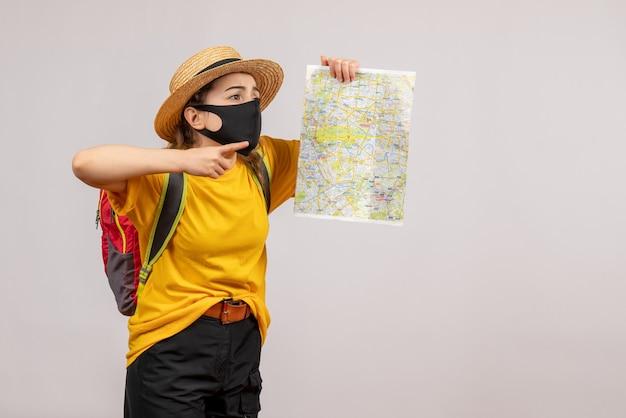 Vorderansicht der niedlichen jungen frau mit dem rucksack, der auf karte auf grauer wand zeigt