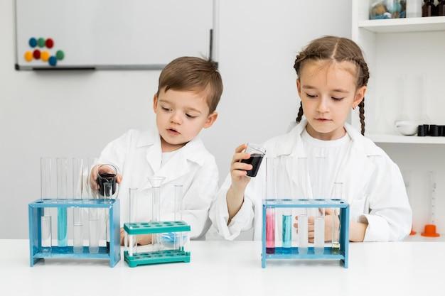 Vorderansicht der niedlichen jungen kinderwissenschaftler mit reagenzgläsern im labor