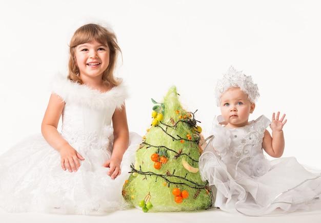 Vorderansicht der niedlichen kinder, die girlande und früchte auf künstliche kiefer setzen.