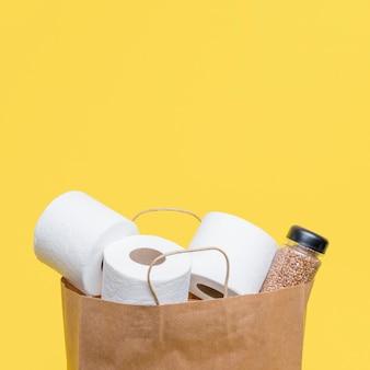 Vorderansicht der papiertüte mit toilettenpapierrollen und kopierraum