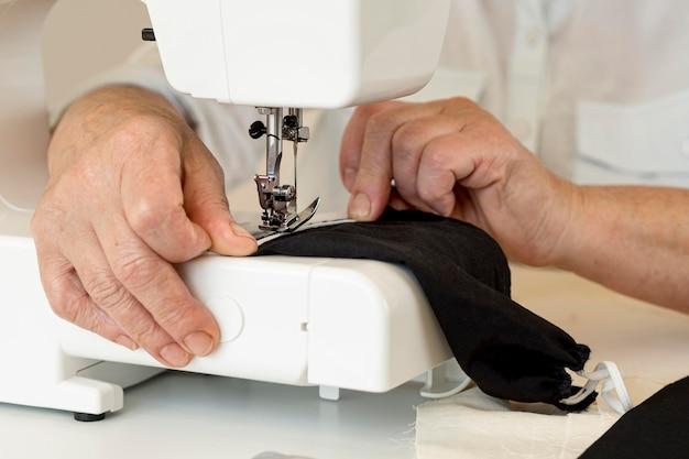 Vorderansicht der person, die nähmaschine für gesichtsmaske verwendet