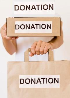 Vorderansicht der person, die spendentasche und kisten hält