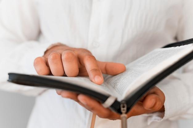 Vorderansicht der person, die vom heiligen buch liest