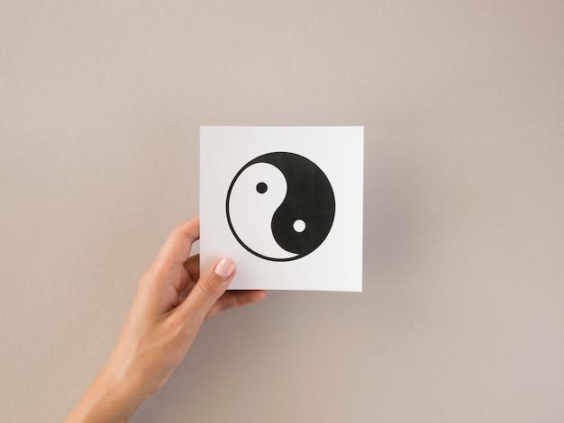 Vorderansicht der person, die ying und yang symbol hält