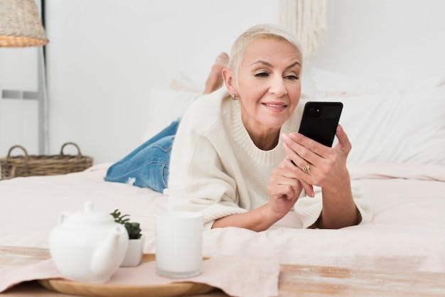 Vorderansicht der reifen smileyfrau im bett, das smartphone hält