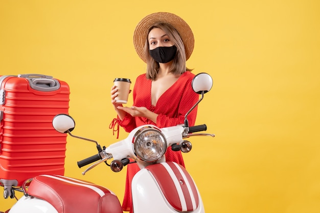 Vorderansicht der reizenden jungen frau mit der schwarzen maske, die kaffeetasse nahe moped hält