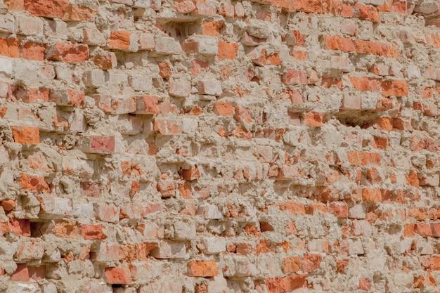 Vorderansicht der rissigen roten lehmziegelmauer eines wohngebäudes