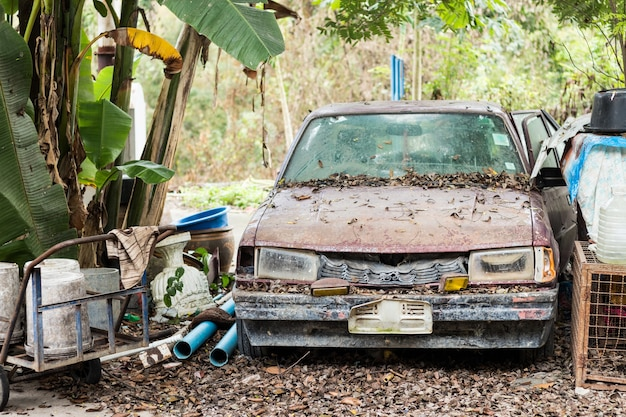 Vorderansicht der rostigen überreste eines alten verlassenen autos.