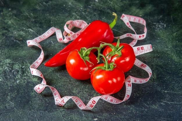 Vorderansicht der roten paprikaschoten der frischen tomaten und des messgeräts auf der oberfläche der dunklen farben mit freiem raum