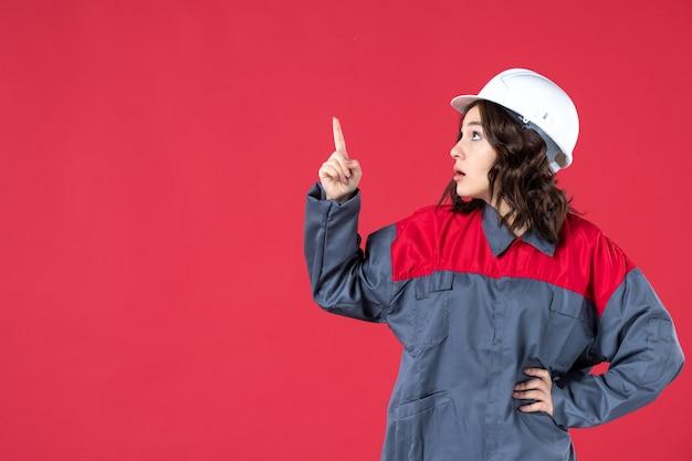 Vorderansicht der schockierten baumeisterin in uniform mit schutzhelm und nach oben auf isoliertem rotem hintergrund zeigend