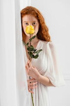 Vorderansicht der schönen frau, die mit einer frühlingsblume aufwirft