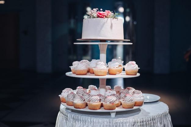 Vorderansicht der schönen hochzeitstorte mit blumen auf dem tisch. leckeres dessert zum feiern. schönes paar im hintergrund. konzept der liebe, süßwaren und keks.