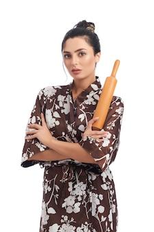 Vorderansicht der schönen jungen frau, die hausrobe trägt, nudelholz hält und. über weiße wand isoliert. konzept der hausarbeit.