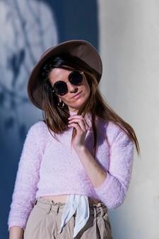Vorderansicht der schönen modischen tragenden sonnenbrille und des hutes der jungen frau, die in der straße bei der aufstellung an einem sonnigen tag steht