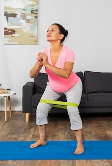 Vorderansicht der schwangeren frau zu hause, die mit gummiband trainiert