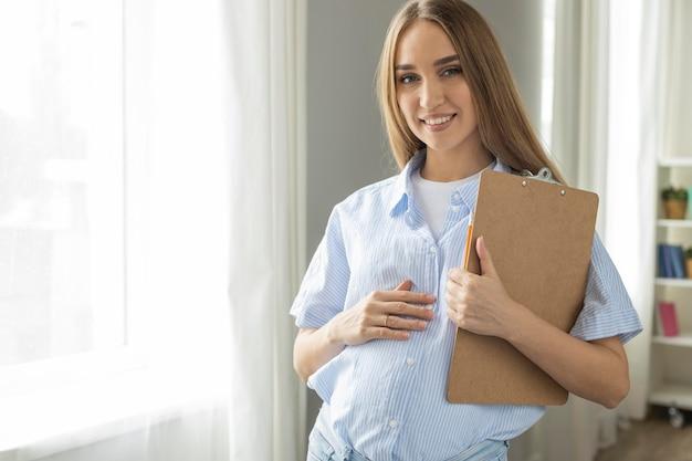 Vorderansicht der schwangeren geschäftsfrau des smileys, die zwischenablage hält
