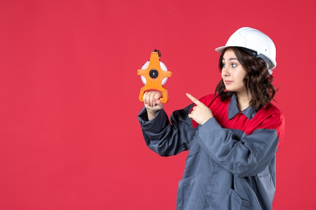Vorderansicht der selbstbewussten architektin in uniform mit schutzhelm, der maßband hält und es auf isolierte rote wand zeigt