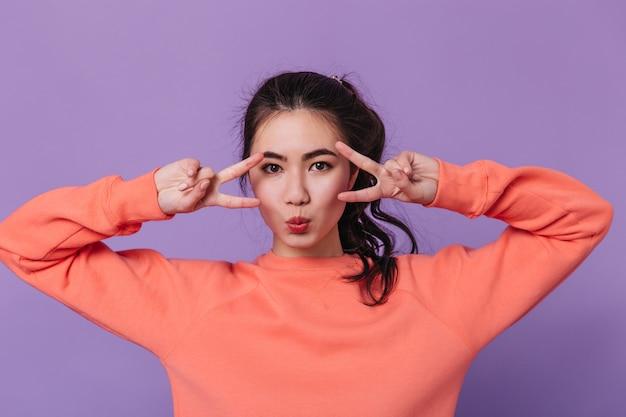 Vorderansicht der sinnlichen asiatischen frau, die friedenszeichen zeigt. studioaufnahme der attraktiven japanischen frau, die auf lila hintergrund gestikuliert.