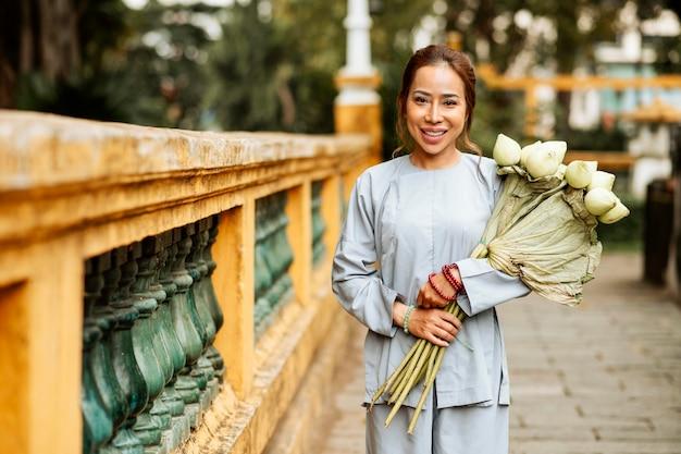 Vorderansicht der smiley-frau am tempel mit blumenstrauß