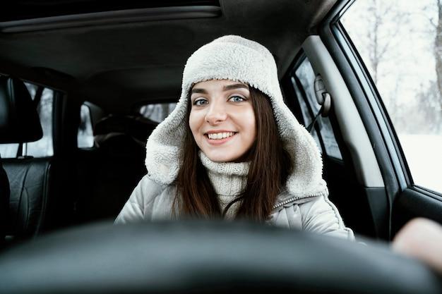 Vorderansicht der smiley-frau, die das auto für auf einer straßenfahrt fährt