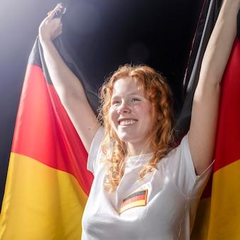 Vorderansicht der smiley-frau, die deutsche flagge hält