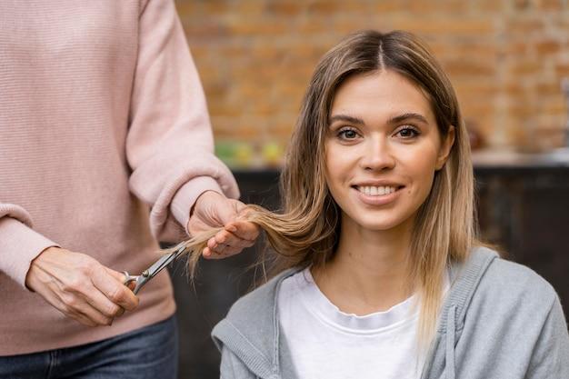 Vorderansicht der smiley-frau, die einen haarschnitt erhält