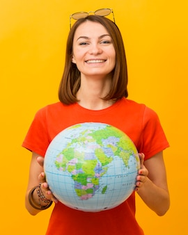Vorderansicht der smiley-frau, die globus hält