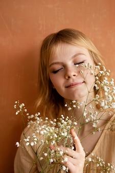 Vorderansicht der smiley-frau, die mit blumen aufwirft