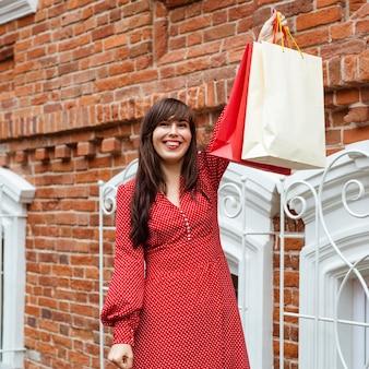 Vorderansicht der smiley-frau, die mit einkaufstaschen aufwirft
