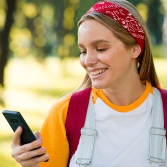 Vorderansicht der smiley-frau, die smartphone im freien betrachtet