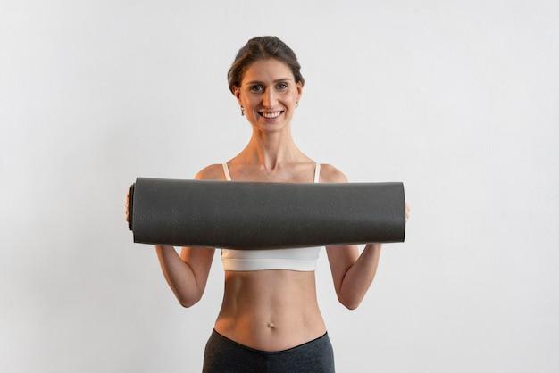 Vorderansicht der smiley-frau, die yogamatte hält