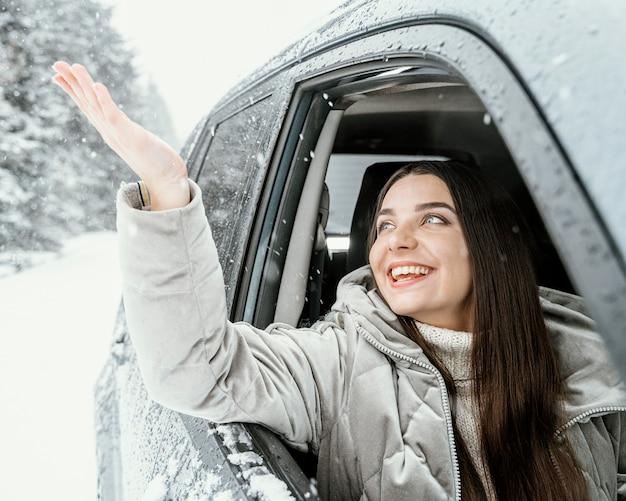 Vorderansicht der smiley-frau im auto während einer straßenfahrt