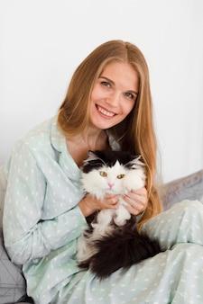 Vorderansicht der smiley-frau im schlafanzug, der katze hält