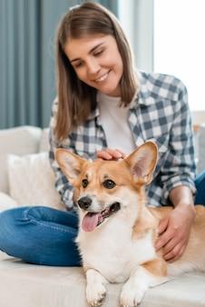Vorderansicht der smiley-frau mit niedlichem hund auf couch