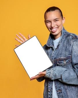 Vorderansicht der smiley-frau mit zunge heraus, die tablette hält