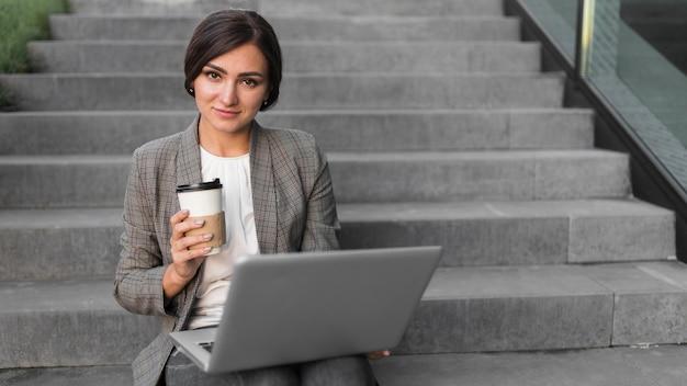 Vorderansicht der smiley-geschäftsfrau, die am laptop auf stufen arbeitet