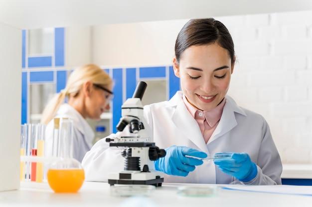 Vorderansicht der smiley-wissenschaftlerin im labor