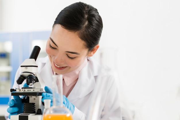Vorderansicht der smiley-wissenschaftlerin und des mikroskops